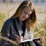 Frau schreibt Tagebuch am Strand